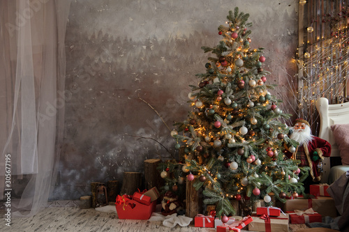 Fototapeta close up photo of a decorated Christmas tree near a white bed with pillows on it obraz