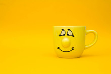 Smiley Yellow Ceramic Cup On Yellow Background. Yellow Mug Empty Blank For Coffee Or Tea. Space For Text