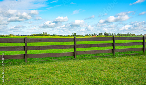 Photo Green fence field and a blue sky. Pastures out of town.