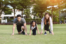 Asian Family Exercising At Park Outdoor.
