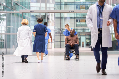 Fotografiet Female Nurse Wearing Scrubs Wheeling Patient In Wheelchair Through Lobby Of Mode