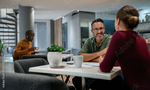 Obraz Wide shot of office canteen. Woman being interviewed by male employer. Background candid people - fototapety do salonu