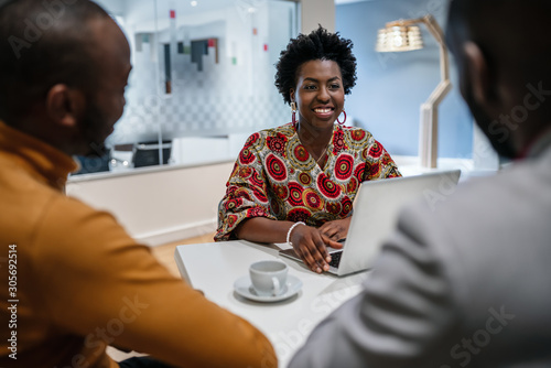 Traditional dressed black african business woman financial bank adviser in meeting with customer