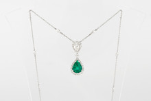 Luxury White Golden Pendant With Green Gemstone And Diamonds On Stand.