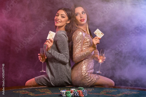 Two girls are playing poker at casino, holding glasses of champagne and cards, sitting on table with chips on it Wallpaper Mural