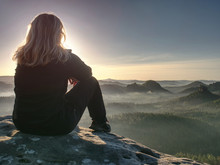 Blond Woman Sitting On Edge Of...