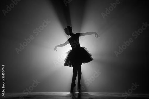 Obraz Professional ballerina dancing ballet in spotlights smoke on big stage. Beautiful young girl wearing black tutu dress on floodlights background. Black and white. - fototapety do salonu