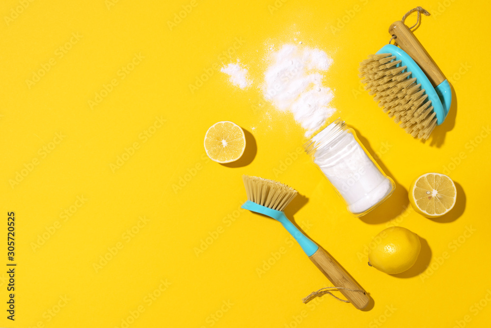 Baking soda, lemon, mustard powder and bamboo brushes against household chemicals products over yellow background. Top view. Copy space. Flat lay. Effective and safe house cleaning