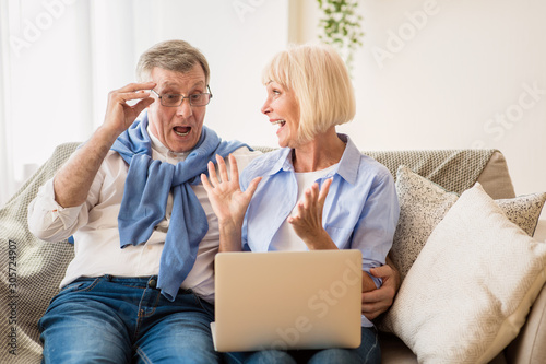 Mature couple surprised by good unbelievable news Wallpaper Mural