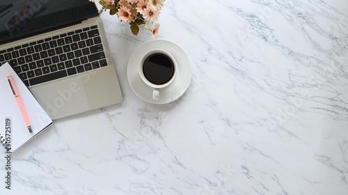 Fotomural Office desk with marble texture and laptop, pen, notebook, coffee with flower on copy space table