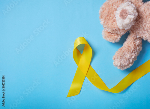 A toy with a yellow Ribbon on light blue background Canvas Print