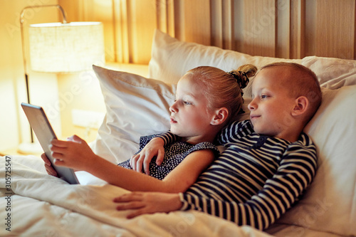 Fotografia, Obraz Little brother and sister lying in bed watching videos together