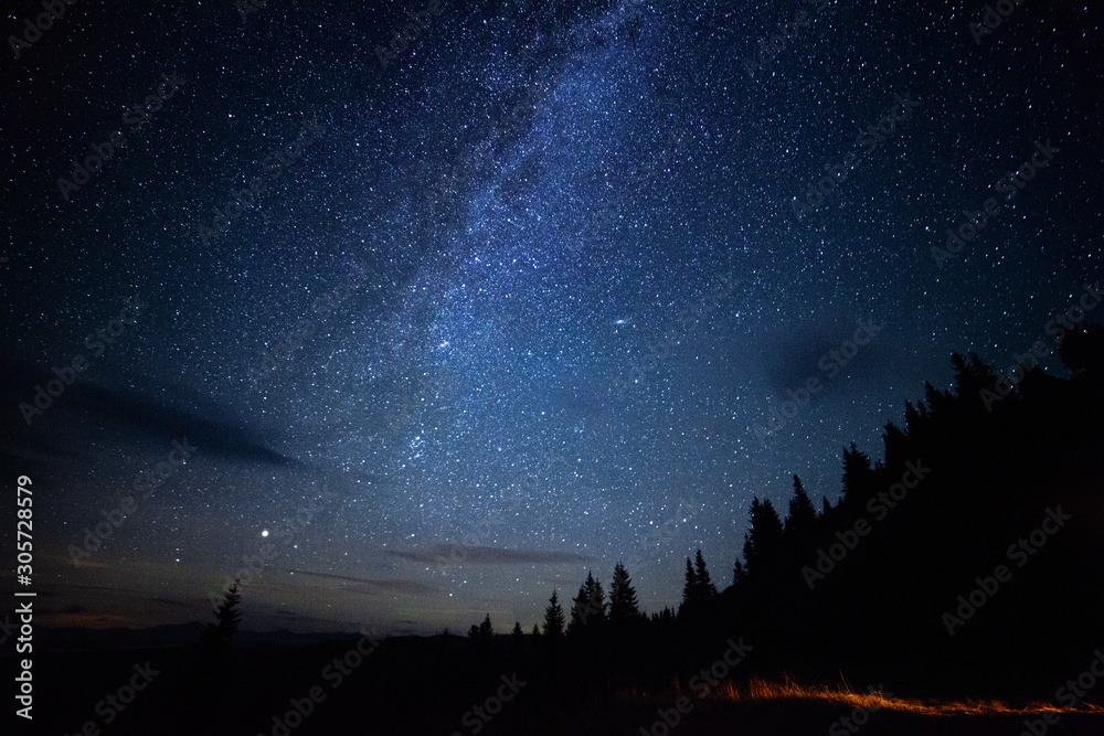 Fototapeta Milky way long exposure astrophotography night sky with stars outdoor scene in mountains forrest. Adventure lifestyle astronomy concept. Cosmic atmosphere universe landcape.