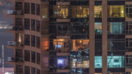 Rows of glowing windows with people in apartment building at night Canvas Print