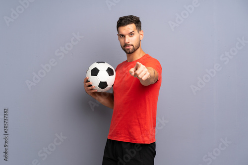 Fotografia Handsome young football player man over isolated white wall points finger at you