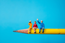 Miniature People, Man And Woman Sitting On Yellow Pencil Using As Business And Social Concept