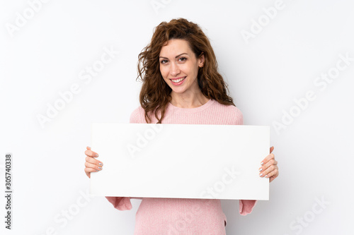 Obraz Young pretty woman over isolated background holding an empty white placard for insert a concept - fototapety do salonu