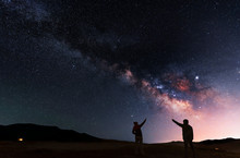 Beautiful Night Landscape. Two Silhouettes Stand On A Hill And Look At The Bright Galaxy Milky Way