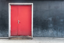 Red Door On A Black Wall Backg...