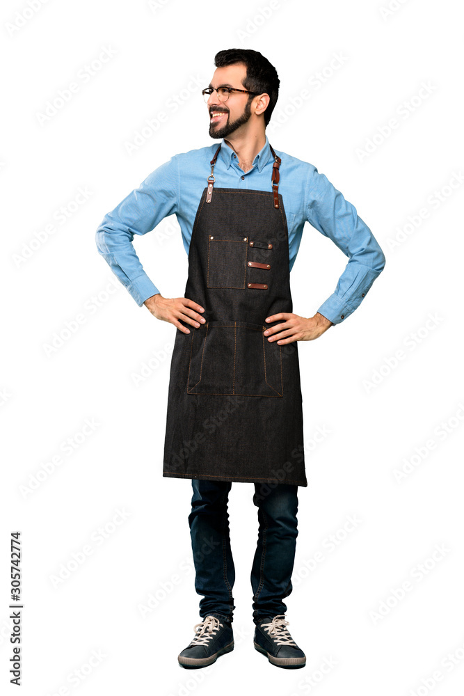 Fototapeta Full-length shot of Man with apron posing with arms at hip and smiling over isolated white background