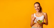 Leinwanddruck Bild - Fit Girl Eating Veggie Salad Standing Over Yellow Background, Panorama