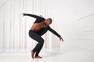 Elegantna plesačica crnaca u crnoj odjeći pleše u svijetloj sobi.