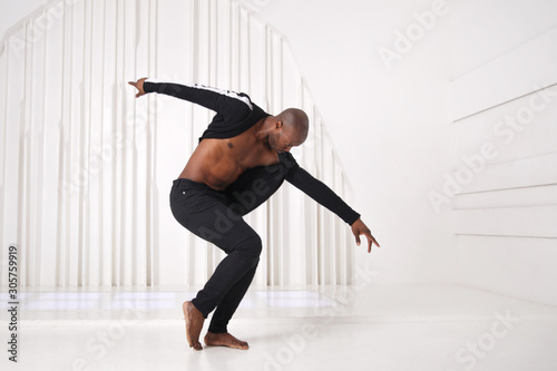 Foto Elegant black man dancer in black clothes is dancing in a bright room