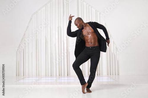 Elegant black man dancer in black clothes is dancing in a bright room Tapéta, Fotótapéta