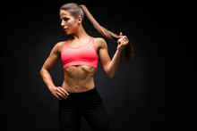 Strong Young Woman With Muscular Abdomen In Sportswear Posing On Black Background.