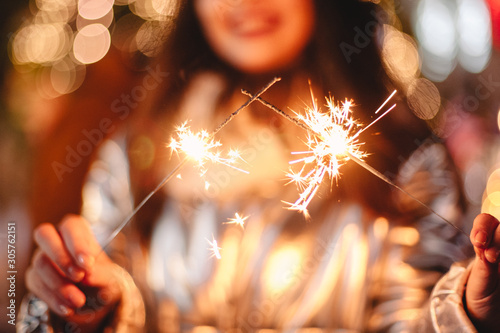 Young woman holding sparklers while standing against Christmas lights in city Fototapet
