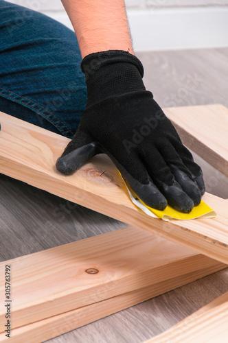 Fototapeta The guy is sanding wooden boards. DIY photophone. obraz na płótnie