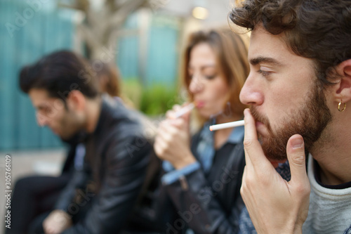 Photo Young people smoking outdoors sitting on a bench