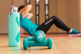Stock photo of two dumbbells and a bottle. In the background a young woman doing sit-ups