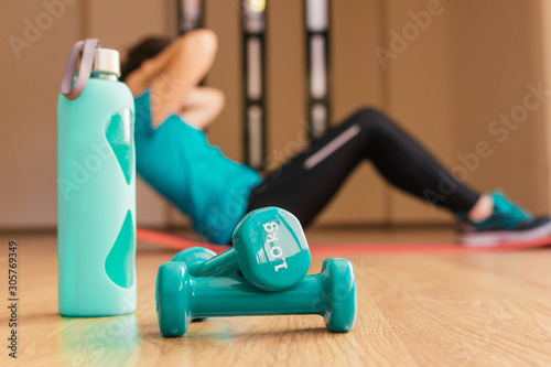 Fototapeta Stock photo of two dumbbells and a bottle. In the background a young woman doing sit-ups obraz