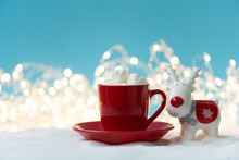 Red Cup Of Hot Chocolate With Marshmallows Decorated Christmas Defocused Lights Reindeer Toy On Snowy Background. Christmas And New Year Holidays Concept. Copy Space
