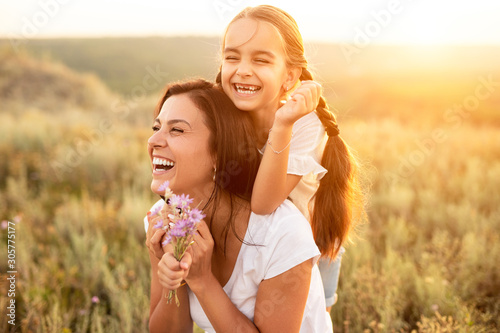 Happy mother and daughter resting at summer field