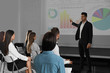 Male business trainer giving lecture in conference room with projection screen