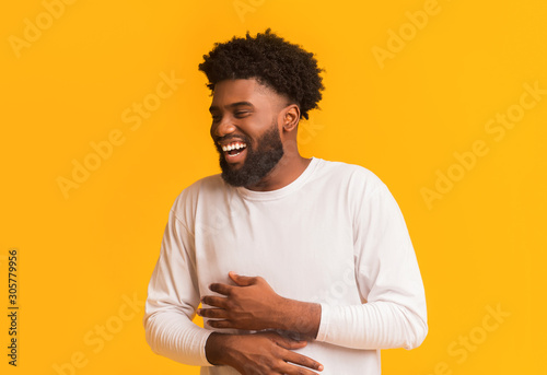 Fotografía  Funny african man laughing out loud, holding his belly