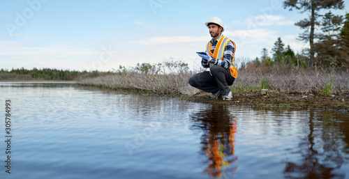 Marine biologist analysing water test results on a tablet in Can - fototapety na wymiar