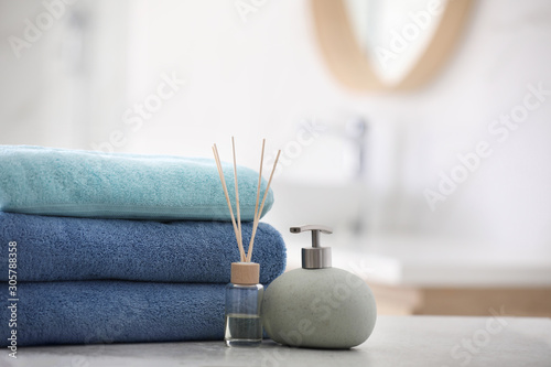 Photo Stack of fresh towels, reed air freshener and soap dispenser on table in bathroo