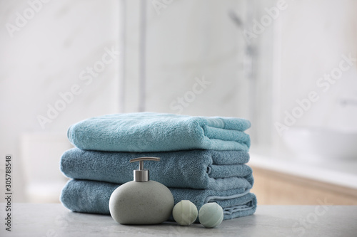 Fototapeta Stack of fresh towels, soap dispenser and bath bombs on table indoors