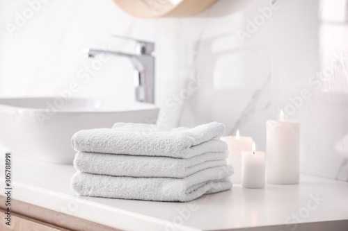 Foto Stack of fresh towels and burning candles on countertop in bathroom