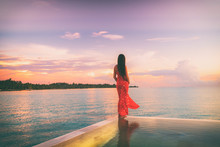 Tropical Beach Paradise Travel Vacation Woman Woman At Dusk Relaxing On Luxury Infinity Pool Resort Hotel Holiday. Summer Getaway Honeymoon Destination.