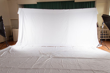 Pull back of set up for professional photography shoot. Volume portrait session. White muslin backdrop 6 metres wide by 3 meters long. Floor cover same size. Shows wrinkles and umbrellas on side.