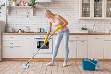Smiling Cleaning Service Woman With Mop Cleaning Floor In Kitchen