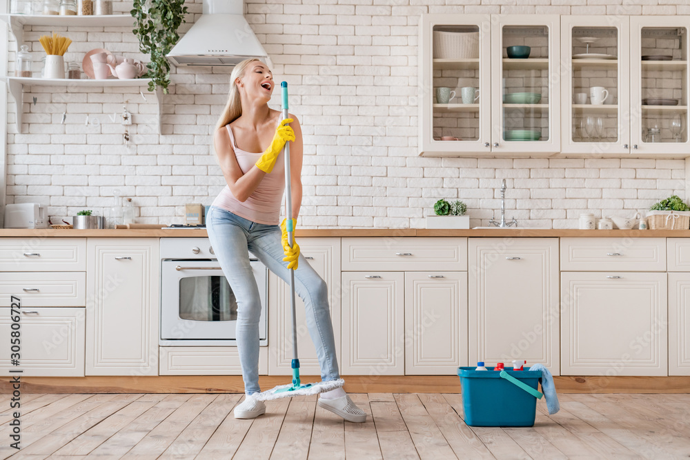Fototapeta Happy woman cleaning home and having fun by singing at mop like in microphone