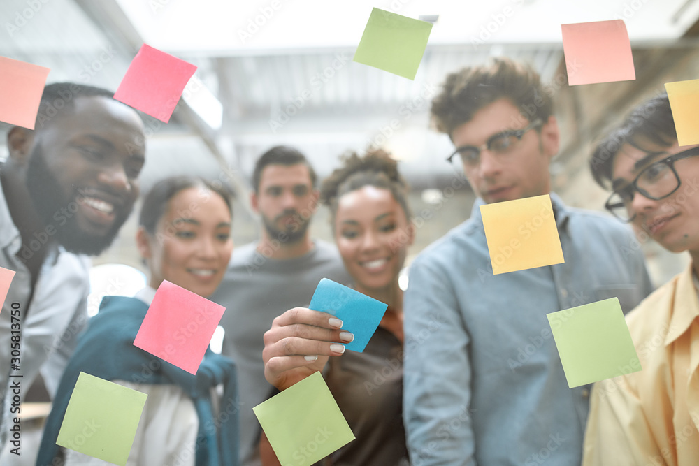 Fototapeta Creative team at work. Group of young and positive coworkers putting colorful sticky notes on a glass window while standing in the modern office