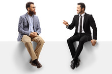 Two Men Sitting On A Panel And Having A Conversation