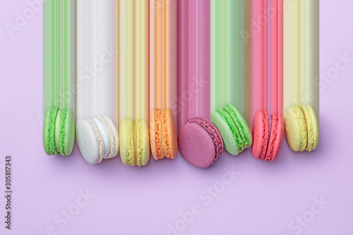 Fotomural Top view of colorful macaron biscuits in a row on pastel color block background,