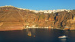 Aerial drone photo of wooden sail boat docked near old port of Santorini island in deep blue sea just below village of Fira, Cyclades, Greece